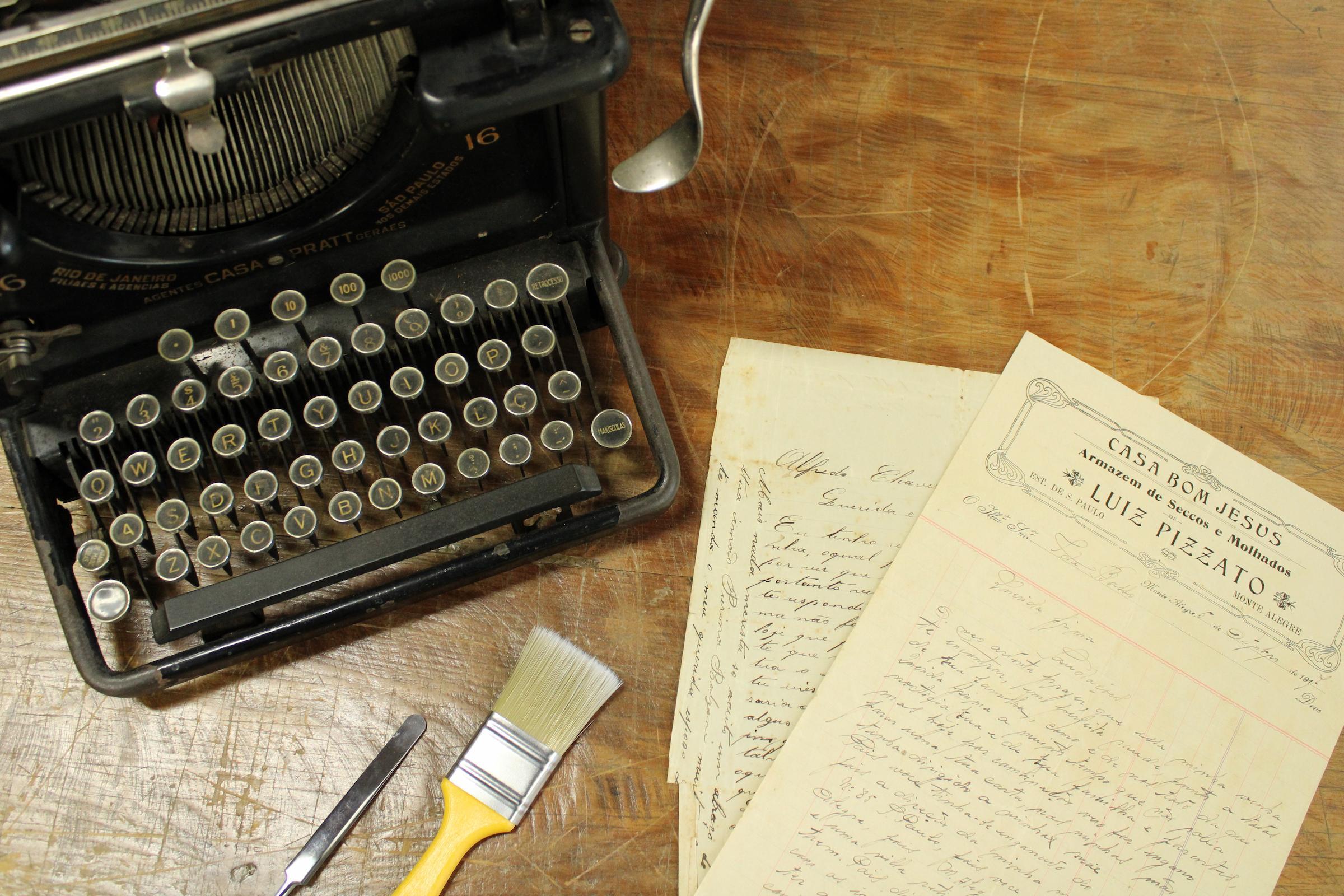 Foto de uma máquina de escrever antiga ao lado de alguns documentos antigos sobre uma mesa.