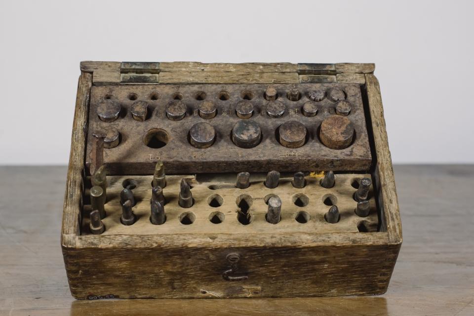 frente de uma caixa de madeira com buracos para encaixe de moldes da prótese dentaria