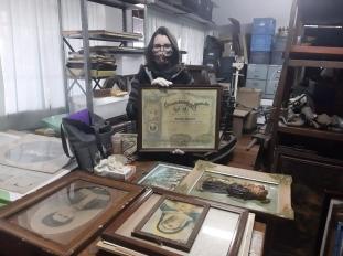 Fotografia de mulher segurando quadro. Em sua frente, diversos quadros e pinturas organizados em uma mesa de madeira.